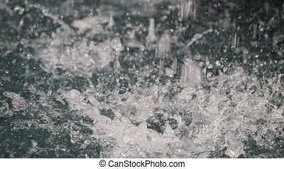 Falling droplets disturbs water surface in slow motion -...