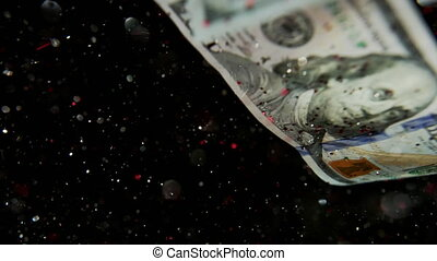 Falling flying american dollar banknotes and flying mixing with the glitter sparkles on a black background in 4K Loopable. High quality falling Dollar banknotes in 4K. Video is Loopable