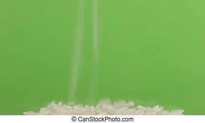 Falling grains of rice on a pile of rice on a green screen.