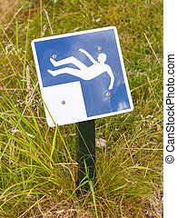 Blue falling hazard sign standing in the grass