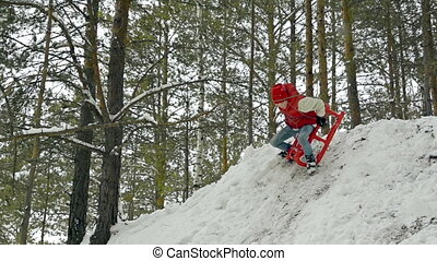 Falling Head Over Heels - Teenage boy riding sledge down the...