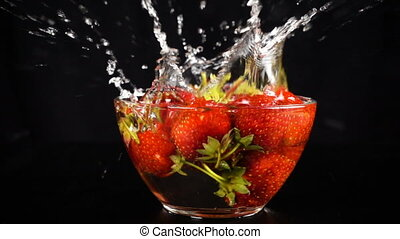 falling many strawberry on glass bowl with water