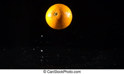 falling orange fruit on black background, slow motion