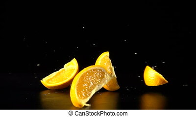 falling orange fruit slices on black, slow motion