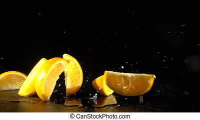 falling orange slices on black background, slow motion