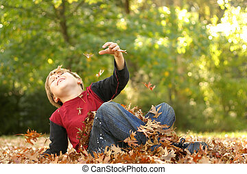An energetic child falls backwards in autumn foliage.