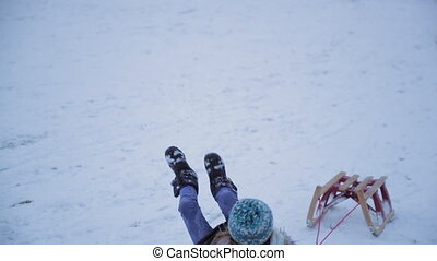Falling Over in the Snow - Little girl is pulling her sled...