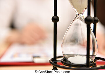 falling sand inside hourglass and working businesswoman