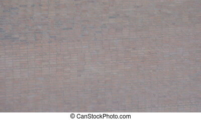 Falling snow, snowstorm on the background of red brick wall