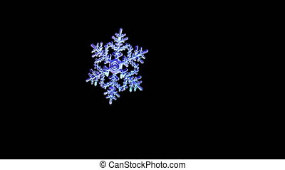 Falling snowflake on black background with alpha channel.