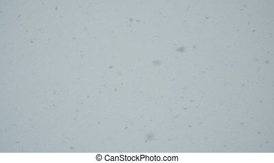 Falling snowflakes against a cloudy sky