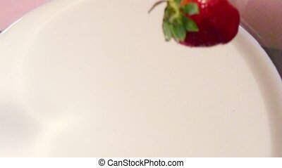 Falling Strawberries in milk in slow motion