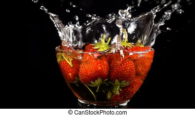 falling strawberries on glass bowl with water splash