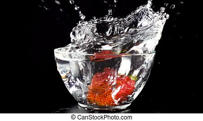 falling strawberry in glass bowl with water splash