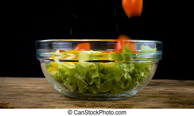 falling tomatoes to salad in glass bowl
