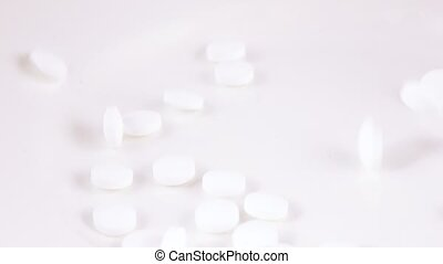 Falling white pills - White pills fall and spin on a white...