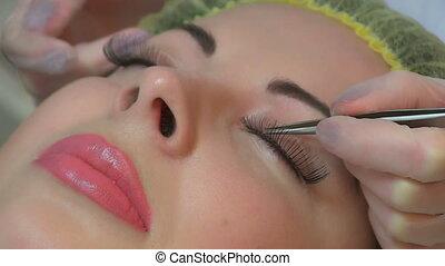 False eyelashes beauty salon procedure - Woman doing...