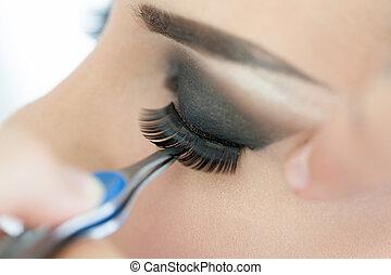 False Eyelashes - Make-up artist applying the false...