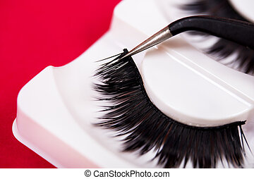 False lashes and  pincers, close up on red background