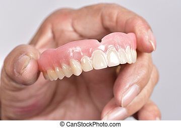false tooth in senior woman's hand