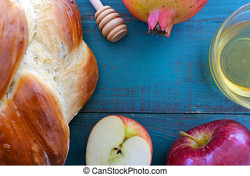 Falt lay view of Round sweet challah, honey jar, red apple...