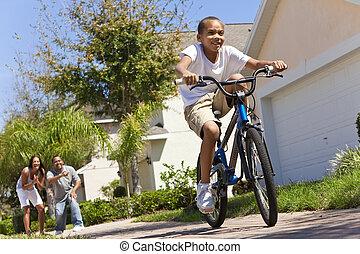 família americana africana, com, menino anda bicicleta, &, feliz, pais