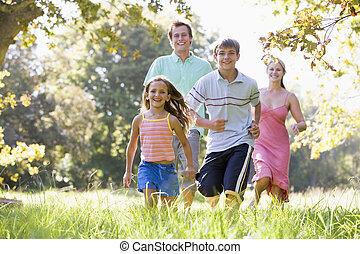 família, executando, ao ar livre, sorrindo
