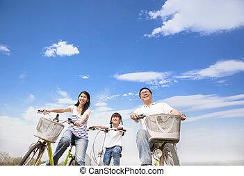 família feliz, bicicleta equitação, com, nuvem, fundo