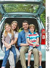 família feliz, de, quatro, sentando, carro, tronco