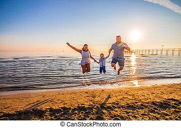 família feliz, salto, praia, ligado, pôr do sol