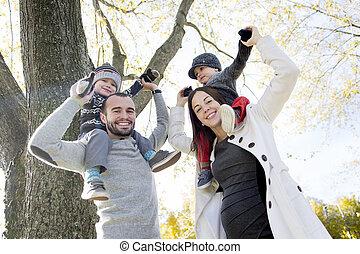 família feliz, tendo divertimento, em, outono, parque