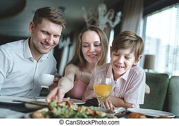 família jovem, comendo pizza