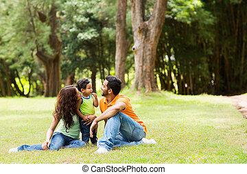 família jovem, sentando, ao ar livre