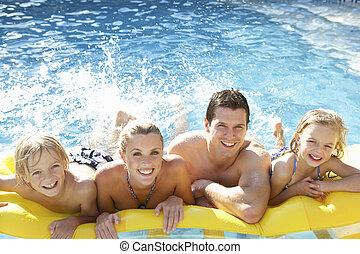 família jovem, tendo divertimento, junto, em, piscina