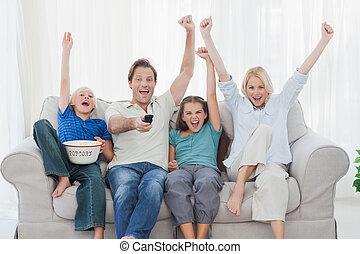 família, olhando televisão, e, braços elevando
