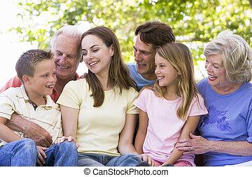 família prolongada, ao ar livre, sorrindo