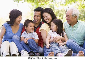 família prolongada, sentando, ao ar livre, sorrindo