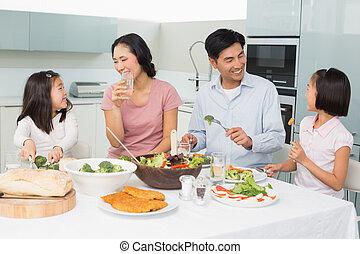 família, saudável, jovem, quatro, desfrutando, refeição, cozinha