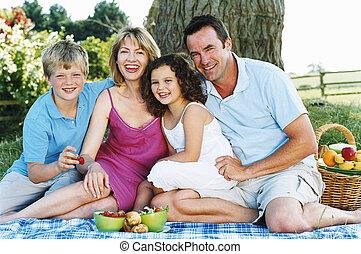 família, sentando, ao ar livre, com, piquenique, sorrindo