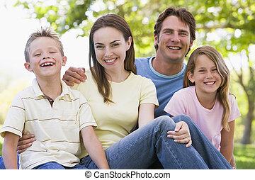 família, sentando, ao ar livre, sorrindo