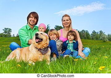 família, sentando, cão, grama verde, feliz