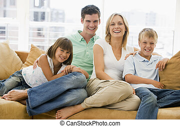 família, sentando, em, sala de estar, sorrindo