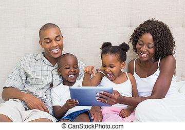 família, tabuleta, cama, junto, usando, feliz