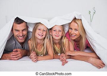 família, tocando, colcha, sob