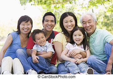 famiglia estesa, seduta, fuori, sorridente
