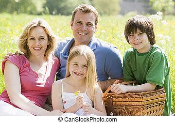 famiglia, seduta, fuori, con, canestro picnic, sorridente