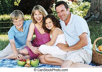 famiglia, seduta, fuori, con, picnic, sorridente