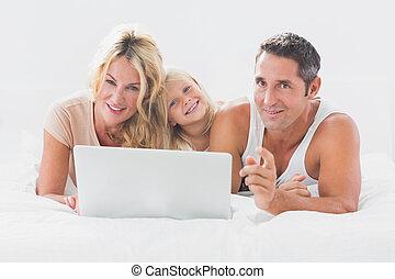 familia , acostado, en, un, cama, con, computador portatil