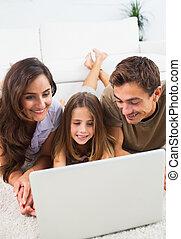 familia , acostado, en una alfombra, con, el, computador portatil