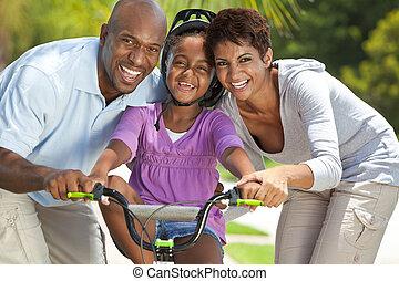 familia americana africana, con, niña, bicicleta de equitación, y, feliz, padres